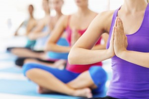 Close-up of young women practicing yoga in health club. Horizontal shot.