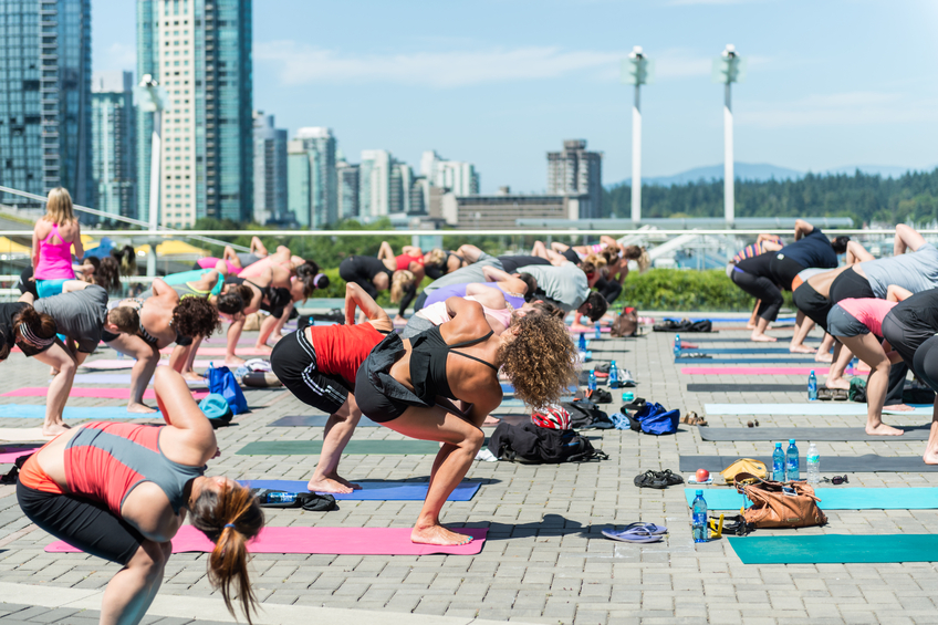 Vancouver, Canada - July 24, 2013: Yoga enthusiasts participate in free lunch hour yoga classes on Jack Poole Plaza at Burrard Landing in downtown Vancouver. The Wednesday series runs from July to August and is presented by Lululemon Athletica.
