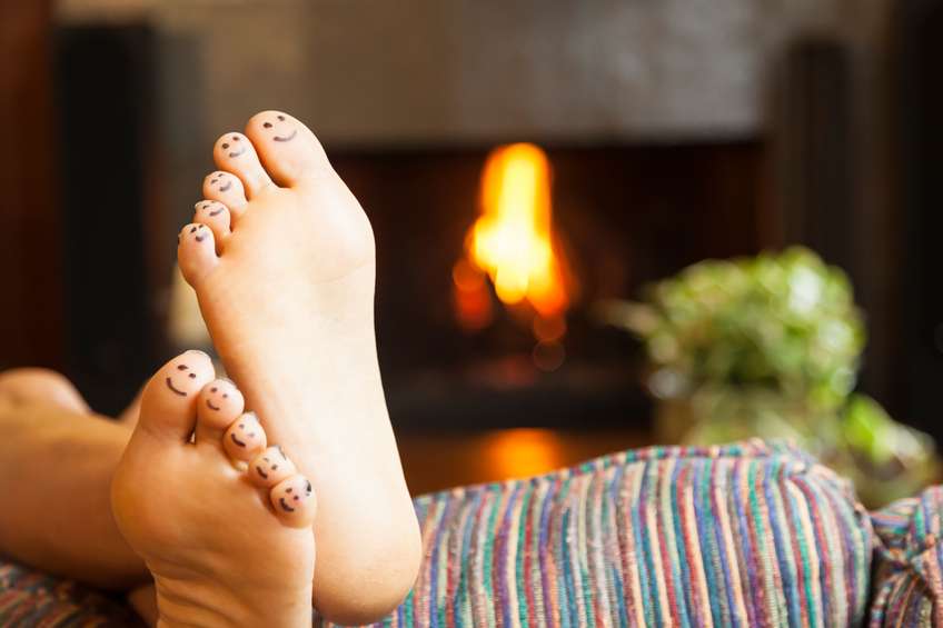 Feet with smiling faces by fireplace
